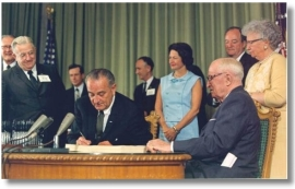 President Lyndon Johnson signs Medicare into law. President Harry Truman, who received the nation's first Medicare card, is seated at the right. (ssa.gov)